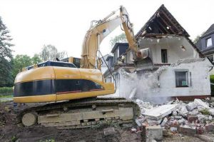 home being demolished by bulldozer