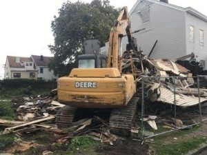 machine cleaning up a building demolition