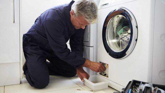 technician fixing leaking washing machine